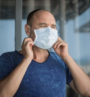 Homem usando máscara facial descartável para evitar infecção viral. proteção contra vírus