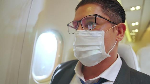 Homem usando máscara facial em um avião