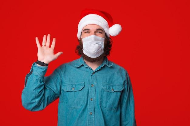 Homem usando máscara facial para distanciamento social e dizendo olá