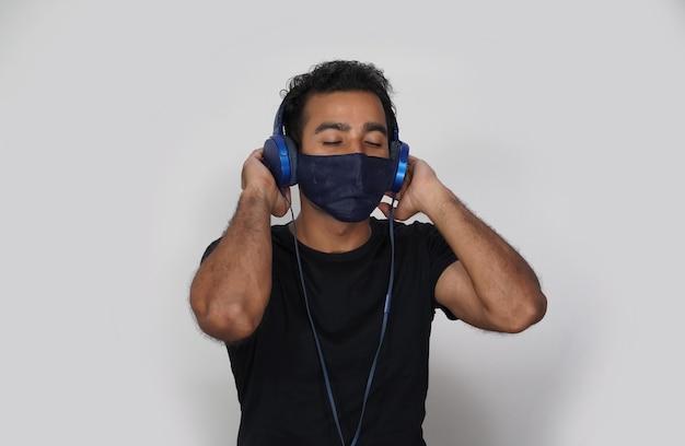 Homem usando máscara, fones de ouvido e curtindo música