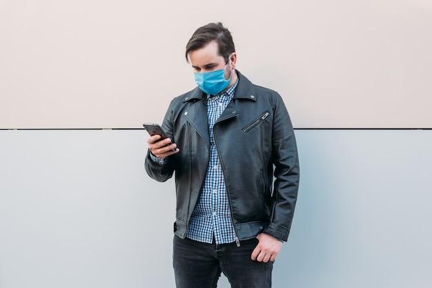 Homem usando máscara higiênica para prevenir infecções, doenças respiratórias no ar, como gripe, 2019-ncov usando smartphone