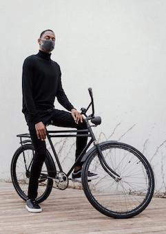 Homem usando máscara médica e andando de bicicleta