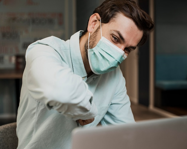 Homem usando máscara médica em videoconferência