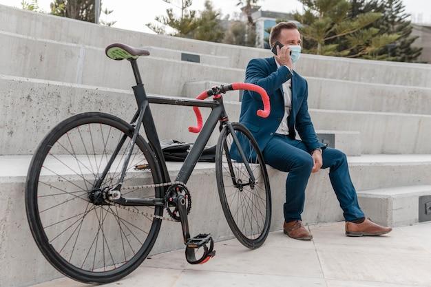 Homem usando máscara médica sentado ao lado de sua bicicleta