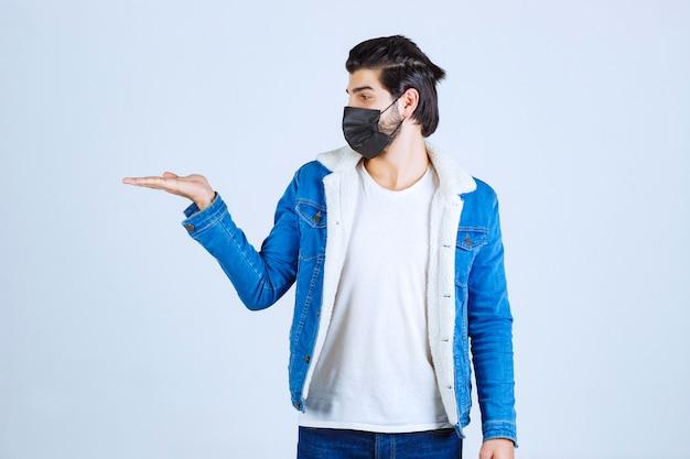Homem usando máscara preta e apontando para a esquerda.