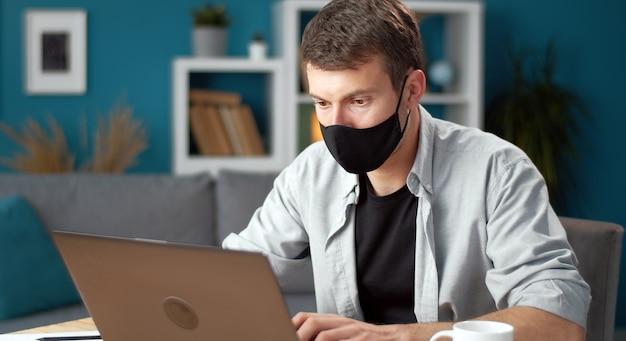 Homem usando máscara protetora, trabalhando em um laptop, ficando em casa durante o surto de vírus