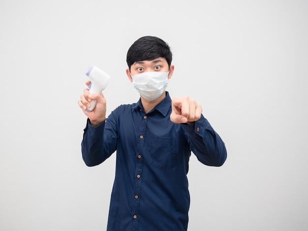 Homem usando máscara segurando um termômetro infravermelho apontando para você em um fundo branco isolado