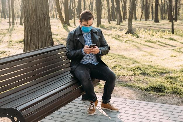 Homem usando máscara usando smartphone, conceito de cuidados de saúde. quarentena do coronavírus.