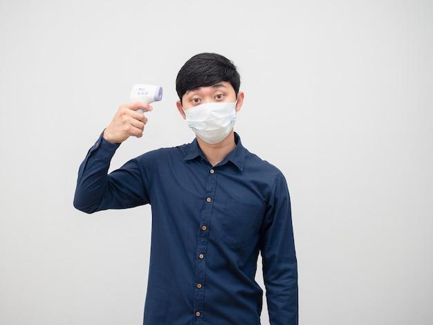 Homem usando máscara usando termômetro infravermelho, verificando na cabeça o fundo branco do retrato
