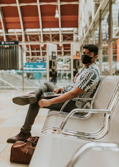 Homem usando máscara usando um laptop em uma estação de trem no novo normal