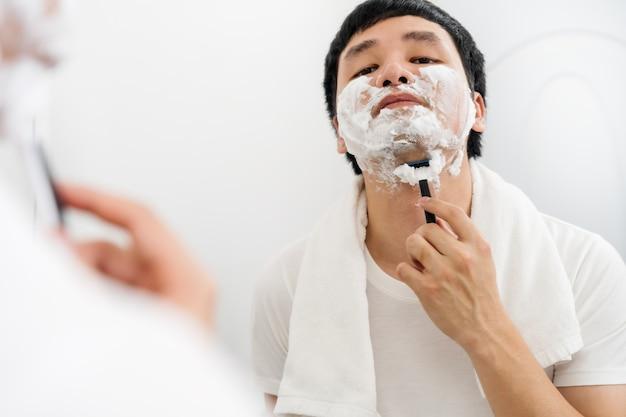 Homem usando navalha para barbear o rosto com espuma creme no espelho do banheiro