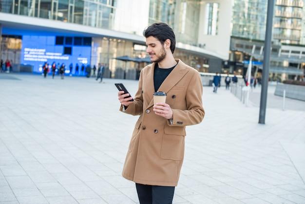 Homem usando o celular e segurando uma xícara de café enquanto caminhava em uma cidade