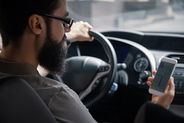 Homem usando o celular enquanto estiver dirigindo.