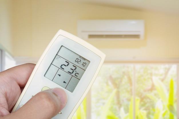 Homem usando o controle remoto liga o ar condicionado