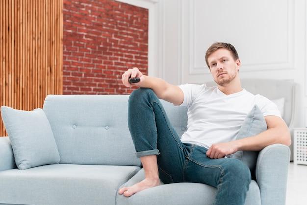 Homem usando o controle remoto para mudar de canal