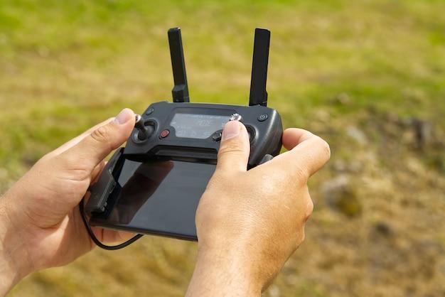 Homem usando o controle remoto para operar o drone atribui terreno borrado.