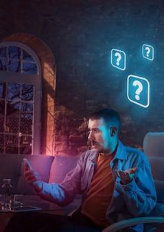 Homem usando o gadget e recebendo notificações de néon em casa à noite sentado na poltrona
