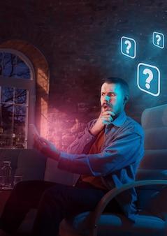 Homem usando o gadget e recebendo notificações de néon em casa à noite