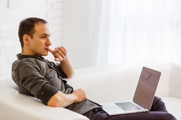 Homem usando o laptop na sala de estar.