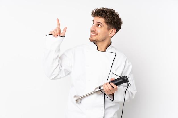 Homem usando o liquidificador na parede branca, apontando com o dedo indicador uma ótima idéia