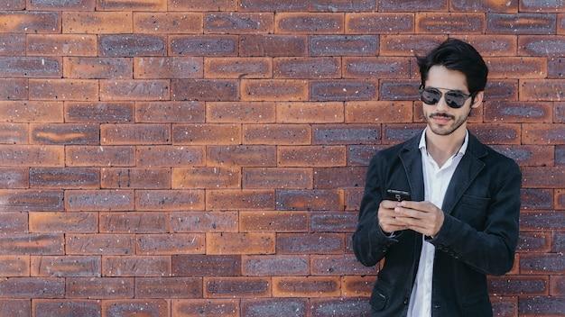 Homem usando o smartphone perto da parede de tijolos Foto gratuita