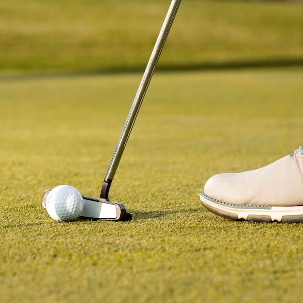 Homem usando o taco para acertar a bola de golfe