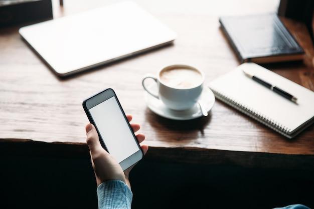 Homem usando o telefone dentro de um restaurante enquanto bebia café.