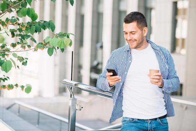 Homem usando o telefone perto do corrimão