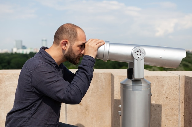 Homem usando o telescópio binóculo panorâmico, olhando para a cidade metropolitana