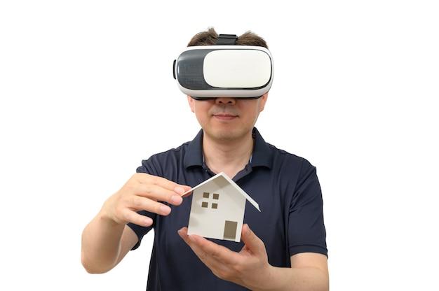 Homem usando óculos de realidade virtual e segurando uma casa de madeira isolada no fundo branco