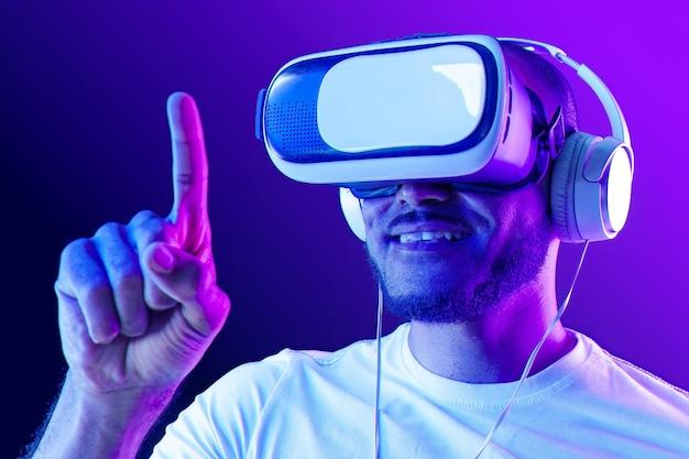Homem usando óculos de rv em luz de néon contra roxo close-up