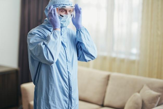 Homem usando óculos de segurança enquanto desinfeta o quarto do hotel