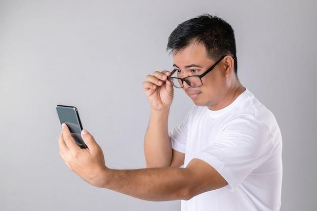 Homem usando óculos e tentando olhar para o smartphone