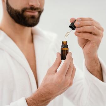 Homem usando óleos naturais no rosto