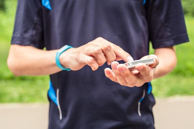 Homem usando pulseira de fitness durante a corrida matinal.
