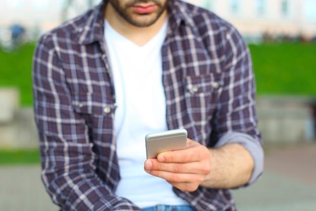 Homem usando seu celular ao ar livre, close-up