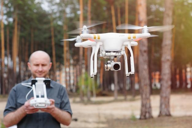 Homem usando seu drone ao ar livre com fundo de floresta