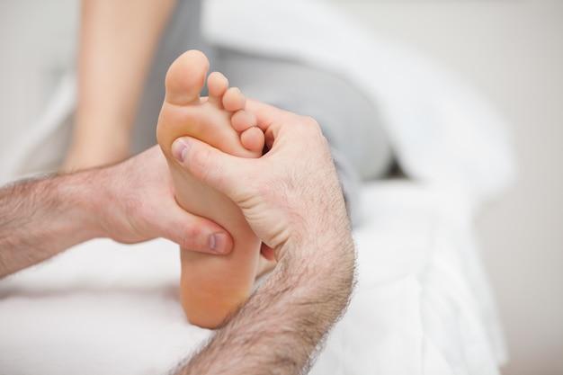 Homem, usando, seu, duas mãos, para, massagem, um pé, em, um, sala