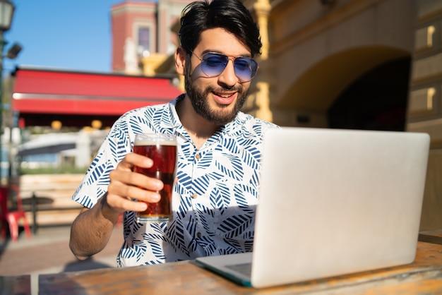 Homem usando seu laptop enquanto bebe cerveja