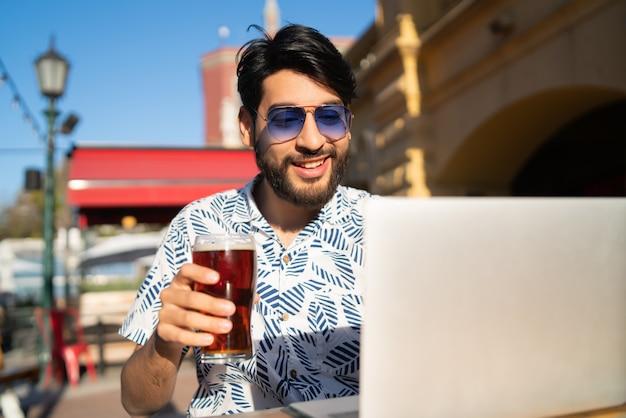 Homem usando seu laptop enquanto bebe cerveja.