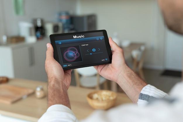 Homem usando seu tablet para um aplicativo de automação residencial