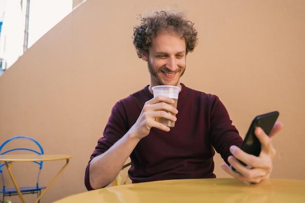 Homem usando seu telefone celular enquanto bebia cerveja