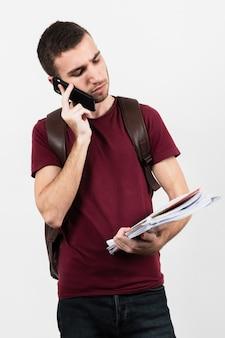 Homem usando seu telefone e olhando suas anotações