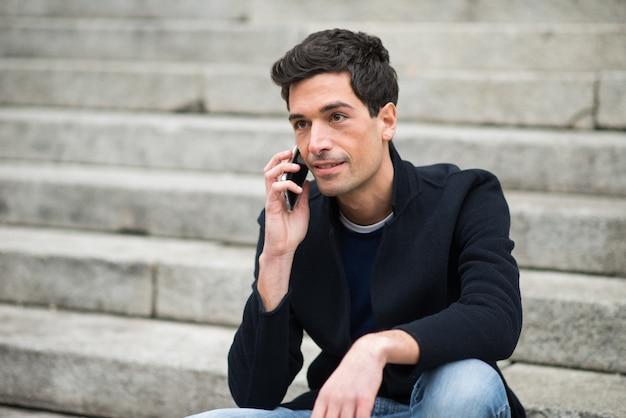 Homem, usando, seu, telefone móvel, em, um, urbano, meio ambiente