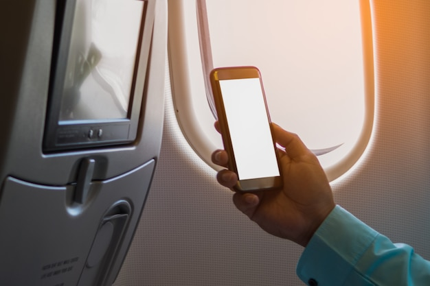 Homem usando smartphone com tela em branco em um avião perto da janela