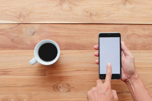 Homem usando smartphone com uma xícara de café na mesa de madeira.