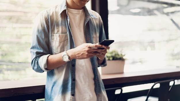 Homem usando smartphone, durante o tempo de lazer.