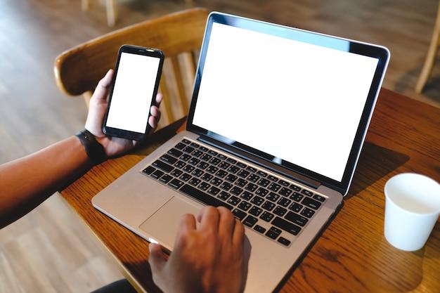 Homem usando smartphone e laptop com telas em branco