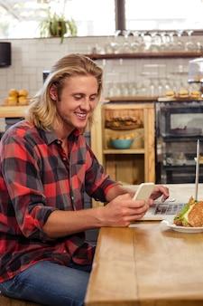 Homem usando smartphone e laptop