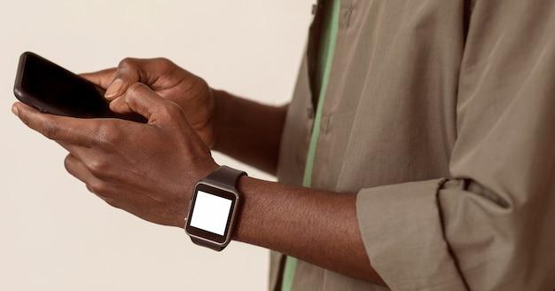 Homem usando smartphone e relógio inteligente